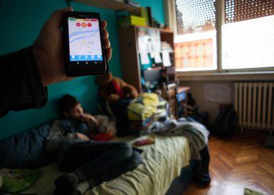 Dok njegov sin gleda televiziju, Mirko Popović testira nivoe kvaliteta vazduha u kući sa AirBeam monitorom za ispitivanje kvaliteta vazduha, za potrebe kampanje protiv zagađenja vazduha, ,,Skini masku mome gradu'' (Eng. Unmask My City). Merenje pokazuje da je srednja vrednost PM2,5 čestica 54 μg/m3 (mikrograma po metru kubnom). Ovo stavlja nivoe čestica u narandžastu kategoriju po standardima indeksa kvaliteta vazduha, odnosno pokazuje da nivoi čestica trostruko premašuju standarde za zdrav vazduh, Svetske zdravstvene organizacije. Mirko je zabrinut, jer zagađenost vazduha u Beogradu (Srbija) utiče na zdravlje njegovih sinova, pa radi kao saradnik nevladine organizacije kako bi poboljšao standarde kvaliteta vazduha. Autorsko pravo: Globalni poziv za klimatsku akciju / Greg McNevin